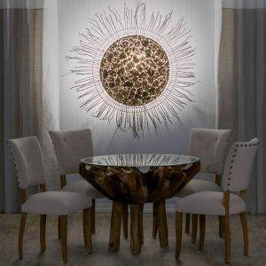 Indonezyjska lampa ścienna Matahari o niekonwencjonalnej formie. Zewnętrzna tarcza stworzona jest z gałęzi, natomiast w środku umieszczone zostały kawałki gliny. Lampa zarazem intryguje i zachwyca. Fot. Dekoria