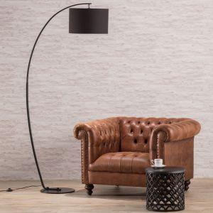 Nowoczesna lampa podłogowa Curve o minimalistycznym designie. Surowa forma to efekt połączenia metalowej, wygiętej w łuk podstawy oraz czarnego abażura. Fot. Dekoria