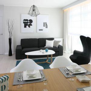 Salon również utrzymany jest w jasnej kolorystyce. Czerń i biel oraz turkusowe dodatki zostały tu bardzo estetycznie skomponowane. Projekt: Anna Maria Sokołowska. Fot. Bartosz Jarosz