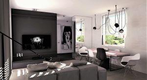 Projekt domu parterowego w Katowicach typu wagon w stylu nowoczesnym. Dominujące kolory to biel, czerń i szarość. Uzupełniająco dekoracyjny beton, cieple drewno i duże formaty graficzne na ścianach.