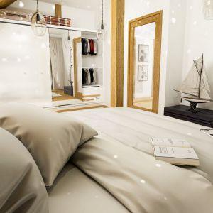 Obszerna zabudowa zapewnia w sypialni miejsce do przechowywania. Duże lustro w szerokiej drewnianej ramie jest ozdobą wnętrza i dodatkowo optycznie powiększa sypialnię. Fot. Dom dla Ciebie Pracownia  Projektowa Archeco