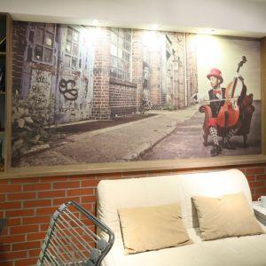 Cegła na ścianie i wyjątkowe zdjęcie przenoszą nas w klimat zabytkowej uliczki. Projekt: Małgorzata Goś, Agnieszka Balińska. Fot. Bartosz Jarosz