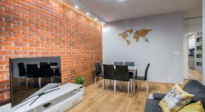 Mieszkanie, w którym króluje cegła, szarość i drewno. Rozległa kuchnia połączona z salonem jest idealnym miejscem na zaproszenie wielu gości i na wspólne gotowanie. Dwie łazienki, jedna w drewnie i bieli do dłuższego relaksu w kąpieli, druga
