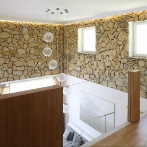 Wyższa część salonu z klatką schodową została wykończona kamieniem. Jest to niezwykle elegancka dekoracja całego wnętrza. Projekt: Magdalena Błaszczak, Fot. Bartosz Jarosz