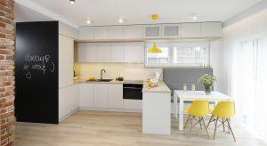 Biała kuchni stanowi subtelne tło da aranżacji otwartej strefy dziennej. Mocnym akcentem stylistycznym są tu kolorowe dodatki.<br /><br />