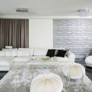 Narożna biała kanapa w połączeniu z dekoracyjnymi panelami 3D w srebrnym kolorze prezentują się niezwykle elegancko. Projekt: Katarzyna Uszok-Adamczyk. . Fot. Bartosz Jarosz