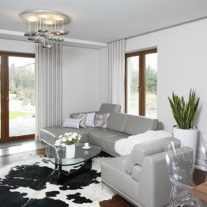 Elegancka skórzana kanapa w szarym kolorze tworzy niezwykłą całość w połączeniu ze szkłem i białymi ścianami. Projekt: Piotr Stanisz. Fot. Bartosz Jarosz