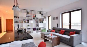 Nowocześnie urządzony apartament zachwyca przestrzenią. Znajdziemy tu dodatki w soczystej czerwieni oraz wiele praktycznych rozwiązań.