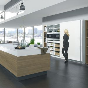 Urządzenia AGD oraz regały z zapasami sprytnie chowają się za drzwiami przesuwnymi, pozostawiając na widoku elegancką i uprzątniętą kuchnię. Fot. Hettich