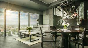 Klimatyczny apartament urządzony został w mocnym, nieco loftowym stylu. Jest to zdecydowanie męski apartament, na tle betonowych ścian i ciemnych mebli dominuje zmysłowa kobieta i stare samochody. Idealnie odnalazły się tu masywne drewniane meble,