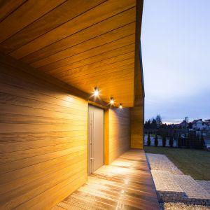 """""""Mroczność"""" domu, została przełamana jasnym, ciepłym drewnem okoume. Wszelkie wycięcia w głównej bryle budynku konsekwentnie zostały wykończone szalówką drewnianą. Fot. Beczak/Beczak/Architektci"""