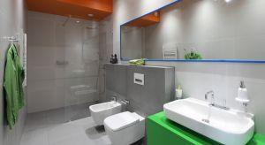 Szarą łazienkę ożywiają barwne akcenty w postaci pomarańczowego sufitu i zielonej szafki podumywalkowej. Nietuzinkowe zestawienie kolorów podkreśla futurystyczny charakter wnętrza.
