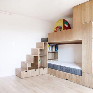 Żeby maksymalnie wykorzystać przestrzeń w pokoju dziewczynek, jedną ze ścian zabudowano trzyosobowym meblołóżkiem. Projekt:  Atelier Starzak Strebicki. Fot. Mateusz Bieniaszczyk