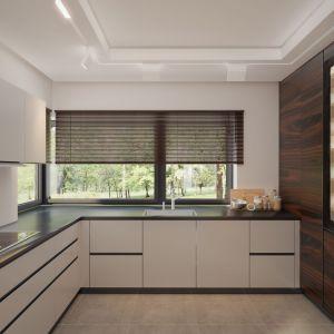 W nowocześnie urządzonej kuchni króluje biel. Bezuchwytowe fronty szafek ciekawie kontrastują z czarnym blatem. Ciekawie zabudowano tu sprzęty AGD – cała ściana jest wykonana z drewna. Projekt: arch. Rafał Zdanowicz, arch. Tomasz Siemieniuk