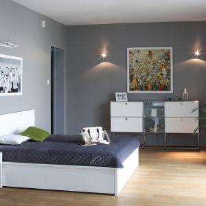 Sypialnia urządzona została w duecie bieli i szarości. Stąd na tle szarych ścian usytuowano proste, minimalistyczne bryły białych mebli oraz zabudowanej w formie podestu wanny. Projekt: Konrad Grodziński. Fot. Bartosz Jarosz