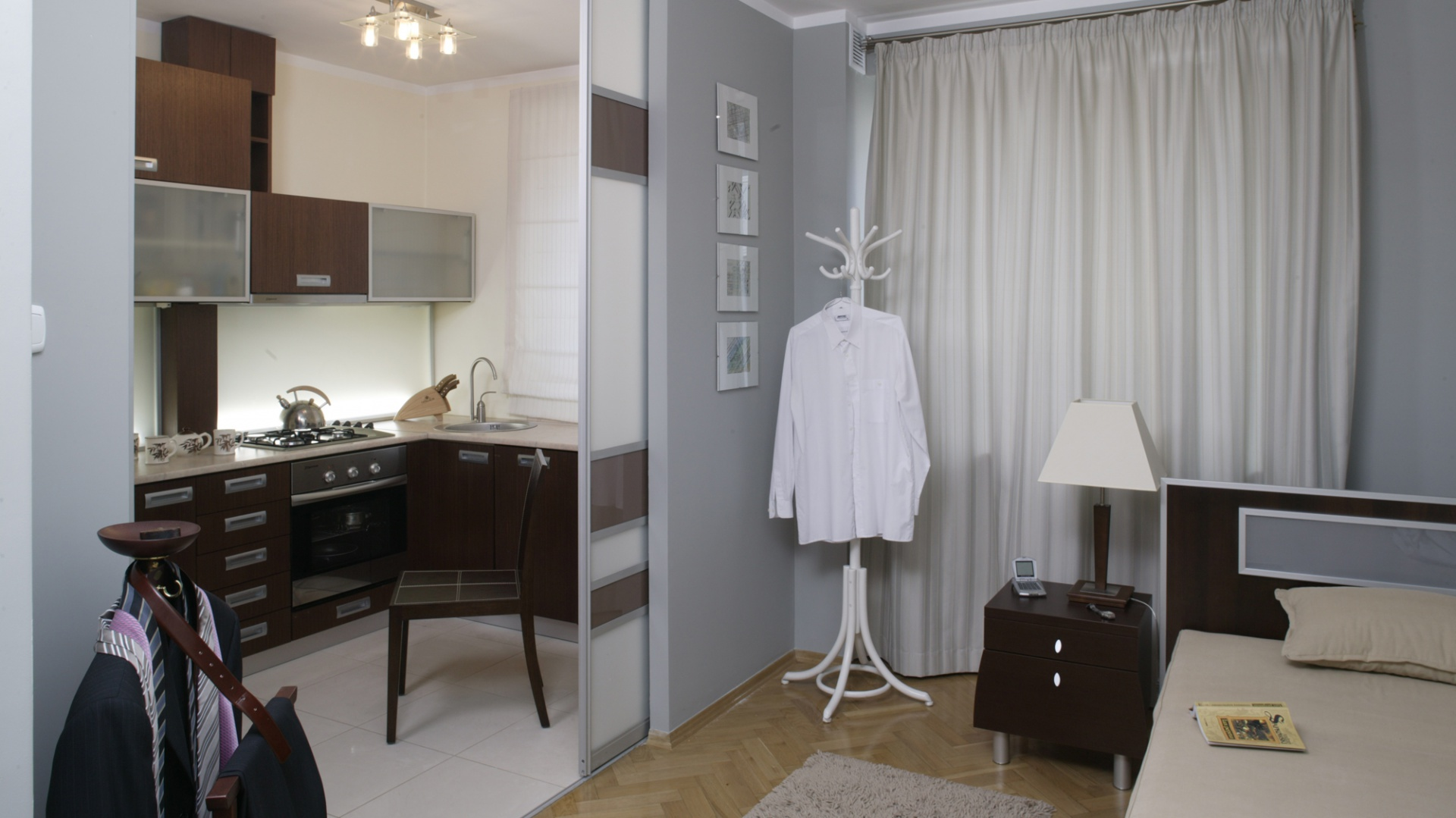Wnętrze kuchni i sypialni dzielą szklane, przesuwne drzwi. Kuchenna zabudowa to połączenie forniru wenge, szkła i stalowych wykończeń. Fot. Bartosz Jarosz.
