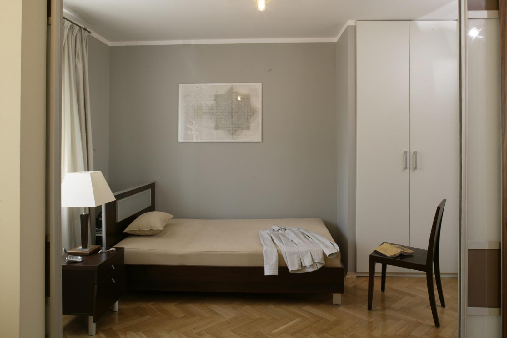 W sypialni znalazły się tylko niezbędne meble: proste łóżko z nocnym stolikiem, wykonane z szarego mdf-u dwie szafy, wieszaki na ubrania oraz krzesło. Fot. Bartosz Jarosz.