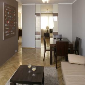 Jadalniany stół stoi na skraju pokoju dziennego. Za przesuwnymi drzwiami znajduje się sypialnia. Do kuchni można przejść z sypialni lub z holu. Fot. Bartosz Jarosz.