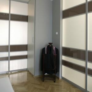 To praktyczne i wygodne rozwiązanie: rozsuwane drzwi (z pasów mlecznego i brązowego szkła), z jednej strony prowadzą do pokoju dziennego, z drugiej – do kuchni. Fot. Bartosz Jarosz.