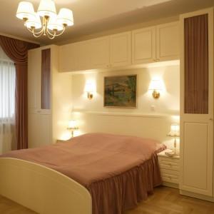 Małżeńskie łoże, przykryte narzutą w kolorze postarzanego różu, zostało ulokowane wśród kremowych szafek. Fot. Monika Filipiuk.