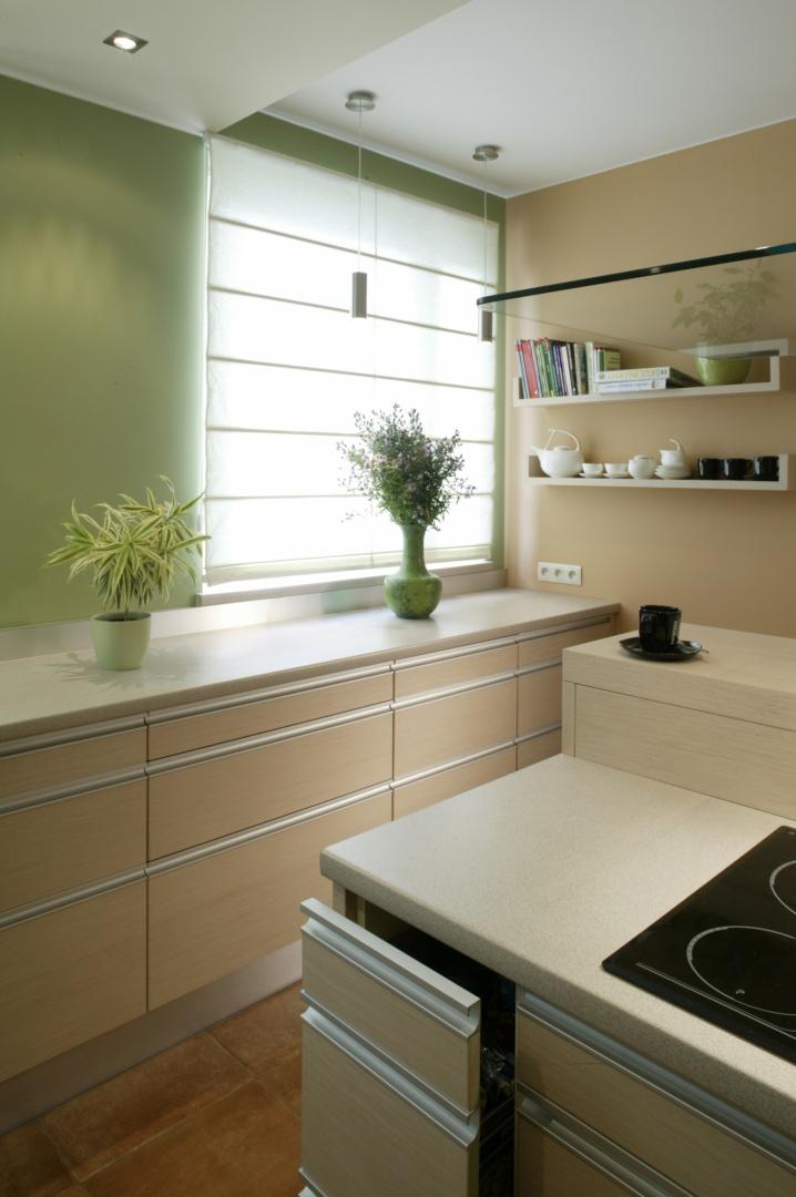 Kuchnia została zaaranżowana w świeżych i jasnych kolorach. Meble z białego dębu milano wykończono aluminiowymi detalami. Fot. Monika Filipiuk.