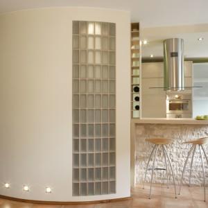 Bezpośrednio do kuchni przylega półokrągła ściana z luksferami ukrywająca łazienkę. Podłogę wyłożono pomarańczowym, ręcznie robionym gresem o rustykalnej stylistyce. Fot. Monika Filipiuk.