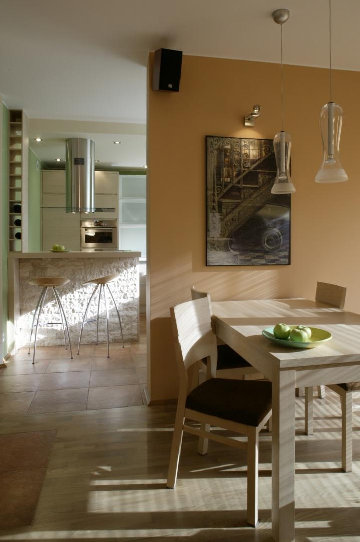 Jadalnia ulokowała się przy ścianie, oddzielającej salon od kuchni. Stanął przy niej jasny, prosty, dębowy stół i krzesła (BRW). Szklane, nieco industrialne lampy to włoskie wzornictwo. Fot. Monika Filipiuk.