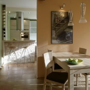 Kuchnię od salonu oddziela ściana, przy której umieszczono jadalnię z prostym stołem i krzesłami (BRW). Do tego dobrano szklane, nieco industrialne lampy, które w ciepły klimat wprowadzają trochę ostrości. Fot. Monika Filipiuk.