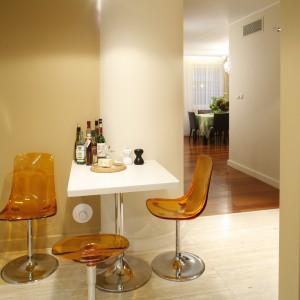 Niewielki stolik śniadaniowy wykonany z corianu (jak wszystkie blaty robocze) wraz z transparentnymi, z pomarańczowymi krzesłami (Soft Line), są efektownym elementem aranżacyjnym. Fot. Bartosz Jarosz.