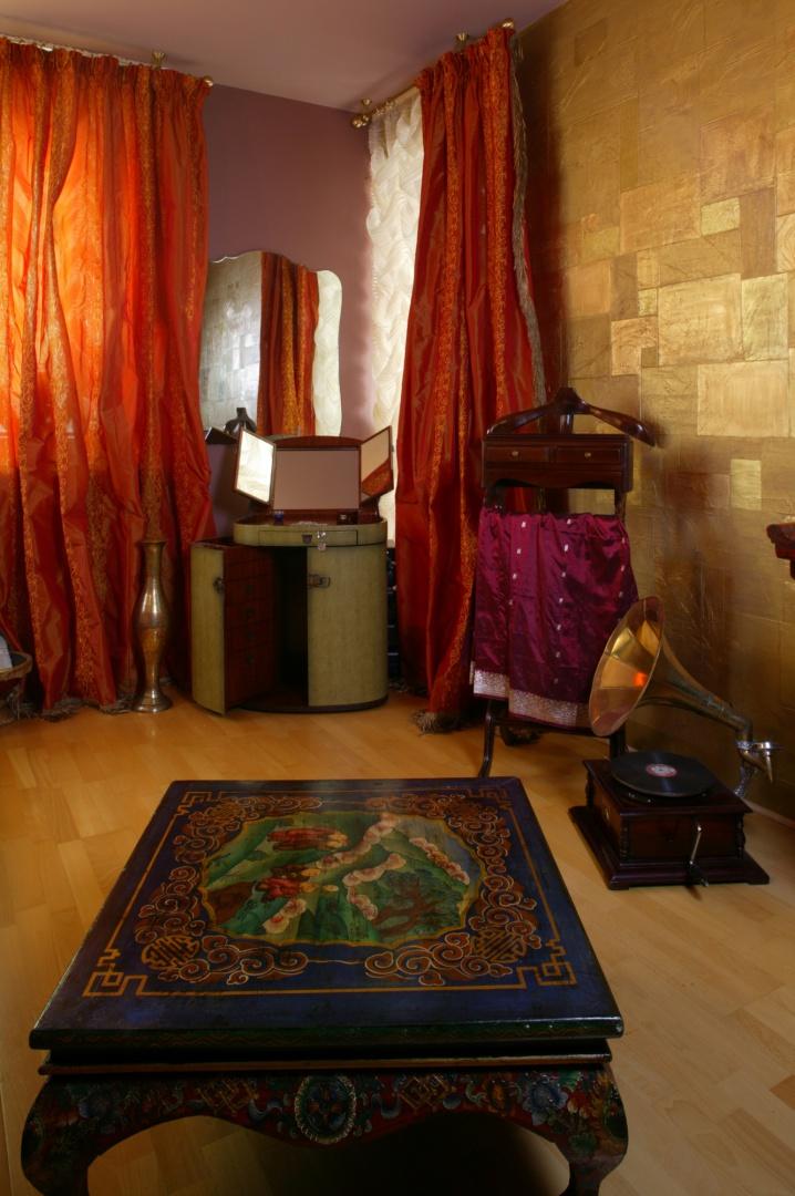 Podróżniczy azyl miłośniczki Orientu. Nie mogło tu zabraknąć toaletki z lustrem i mnóstwem szuflad na biżuterię. Pośrodku pokoju ulokowano bogato zdobiony stolik kawowy. Fot. Monika Filipiuk.
