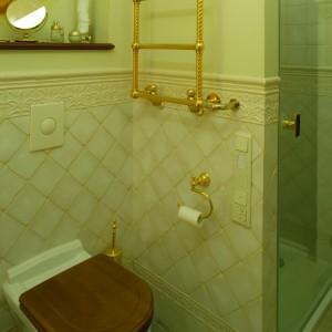 Strefę higieniczną przesłania ścianka kabiny prysznicowej. Zawieszony na niej złocony grzejnik przypomina bardziej dekoracyjny wieszak niż urządzenie techniczne.