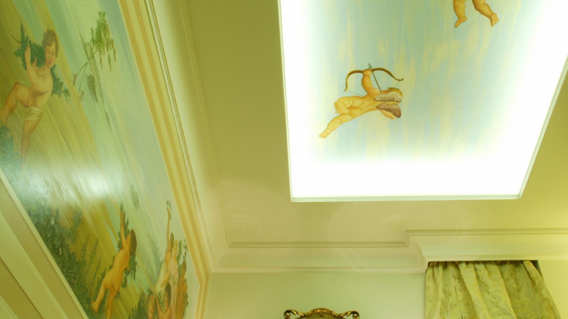 Podświetlony po obwodzie podwieszony sufit stwarza wrażenie, że amorki unoszą się w powietrzu, a pomieszczenie jest znacznie większe i z oknem na błękitne niebo.