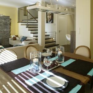 Jadalniany stół zajął miejsce przy dużym oknie, pomiędzy kuchnią i salonem. To duży dębowy mebel z widocznymi słojami i przebarwieniami. Podobnie jak otaczające go krzesła utrzymany jest w stylistyce retro. Fot. Monika Filipiuk.