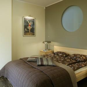 Jasnym, prostym meblom w sypialni (kolekcja Malm, Ikea) towarzyszą ciemniejsze poduchy i narzuta oraz high-techowe lampki nocne. Fot. Monika Filipiuk.