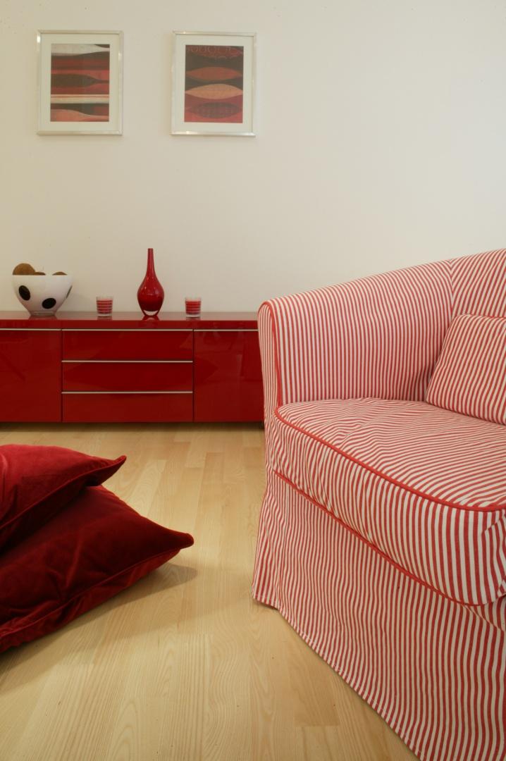 Soczyste dodatki w głębokim kolorze amarantowej czerwieni i pudrowego różu sprawiają, że wnętrze mieszkania pulsuje życiem. Fot. Monika Filipiuk.