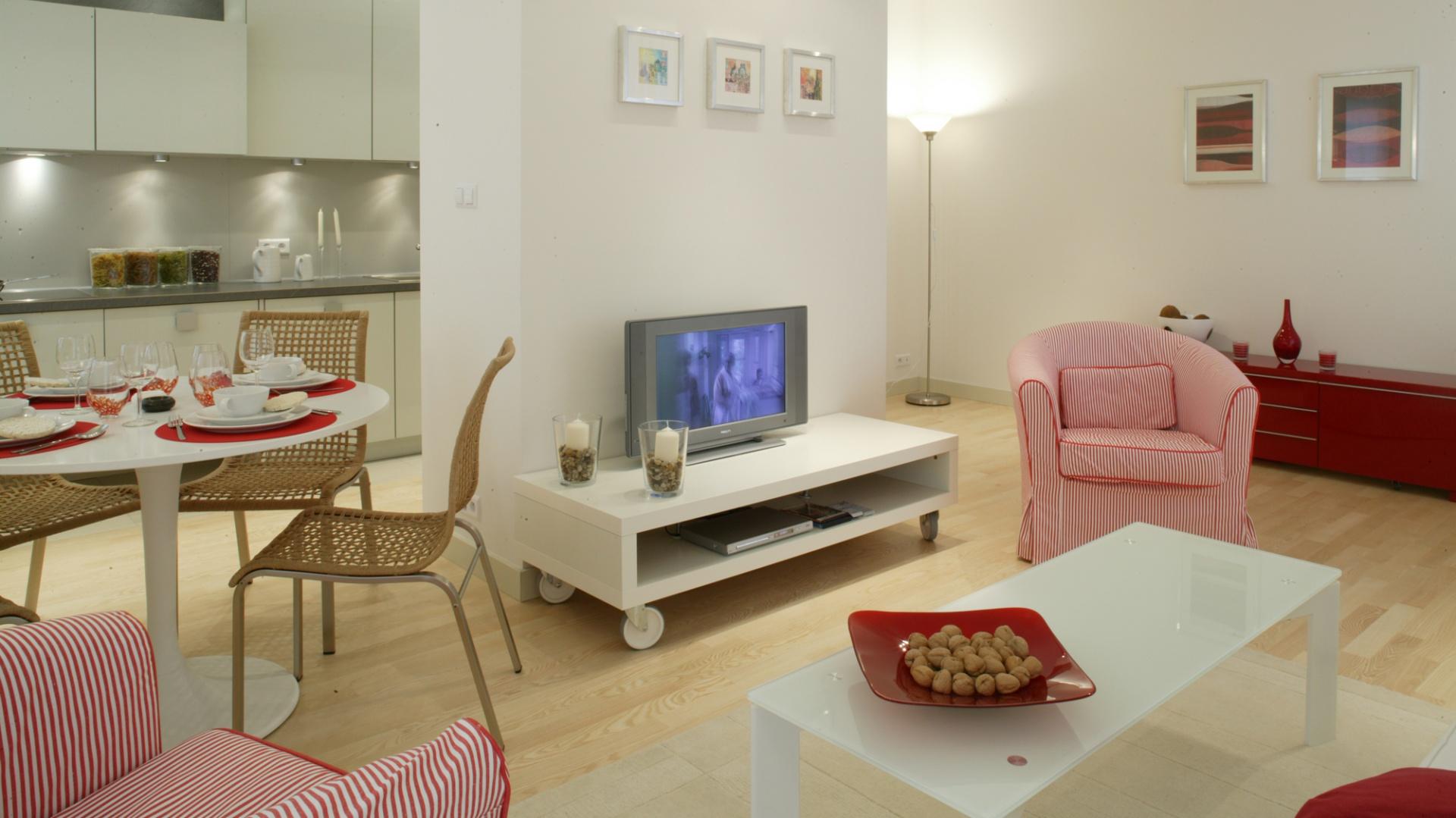 Strefy funkcjonalne w dziennej części mieszkania oddziela krótka ścianka działowa, przed którą ulokowano mobilną szafkę z telewizorem. Jasne przestrzenie salonu i kuchni ożywiają czerwone i amarantowe dodatki oraz część sprzętów. Fot. Monika Filipiuk.