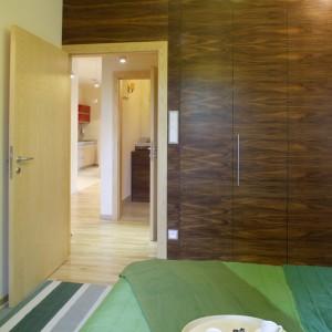 Zabudowa wnękowa w kolorze amerykańskiego orzecha otacza wyjście z sypialni. Ciemnobrązowy, mocno usłojony materiał, kontrastuje z jesionową podłogą i drzwiami. Fot. Bartosz Jarosz.