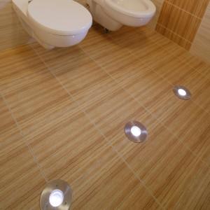 Podłogę i ściany pokrywają płytkami z tej samej kolekcji, w dwóch współgrających kolorach. Lampki  w podłodze to oryginalna ozdoba wnętrza. Fot. Monika Filipiuk.