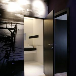 """Kiedy drzwi łazienki są  otwarte, jej ostro kontrastujące z kolorystyką klatki schodowej wnętrze, robi wrażenie autentycznego """"światła w tunelu"""". Fot. Monika Filipiuk."""