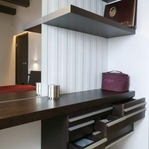Ściana, za gustownie zaprojektowaną, podwieszaną toaletką z przyczernianego dębu, z jednej strony została przyozdobiona szklanymi pasami, z drugiej zaś przykryta lustrem. Fot. Monika Filipiuk.