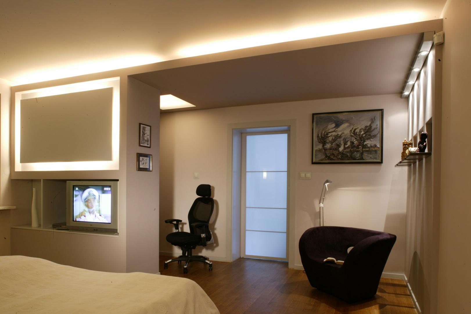 Gdy trzeba, sypialnia może służyć jako miejsce rozrywki (z łóżka można oglądać filmy), ale także i pracy (minigabinet zaaranżowano za ścianką). Uwagę zwraca oświetlenie. Światło sączy się z lampek umieszczonych w podwieszanym suficie. Fot. Monika Filipiuk.