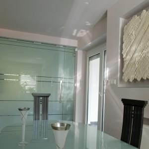 Po wsunięciu w ścianę drzwi, jadalnia staje się częścią salonu. Po ich zamknięciu to oddzielne pomieszczenie, w którym króluje stół ze szklanym blatem i krzesła z oparciami, przypominającymi greckie kolumny. Fot. Monika Filipiuk.