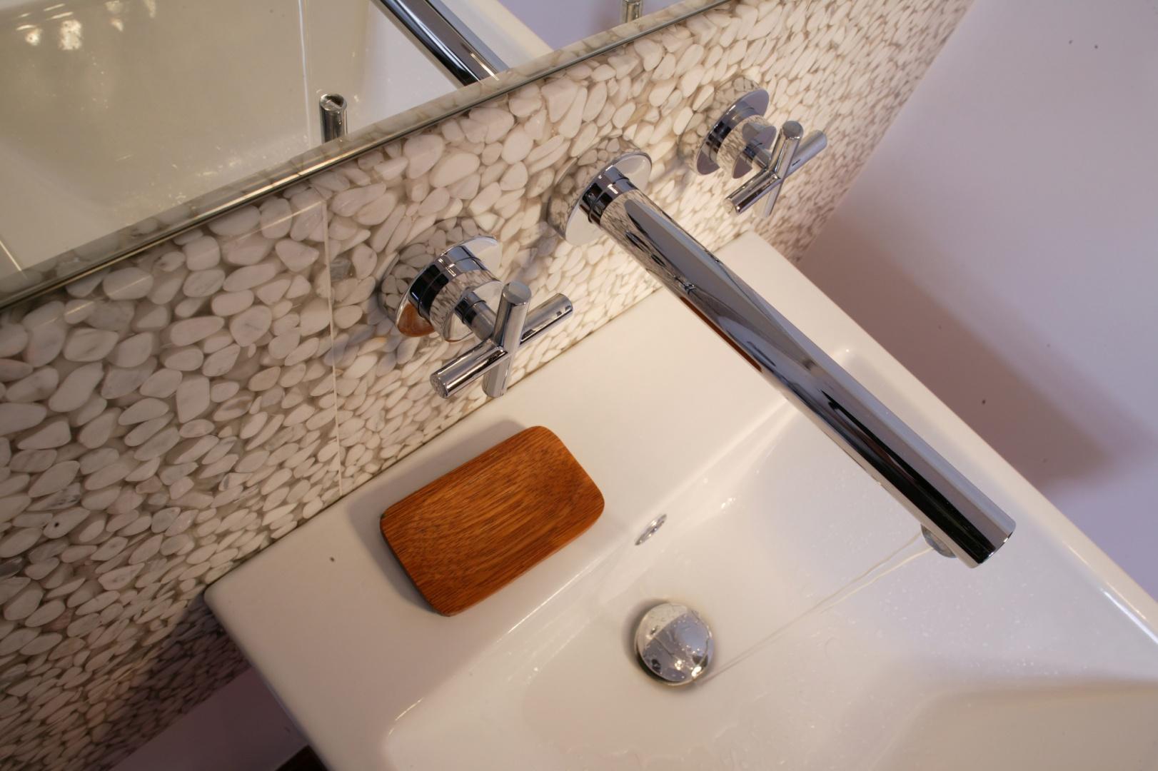 Baterię umywalkową (z mieszaczem zainstalowanym pod tynkiem) wyróżnia minimalistyczne wzornictwo. Proste linie jej wylewki oraz krzyżowych kurków idealnie wpisują się w klimat łazienki. Fot. Monika Filipiuk.