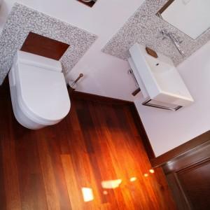 Cała podłoga wykończona został odpowiednio zaimpregnowanym drewnem tekowym. Jego złocistobrązowy odcień podniósł temperaturę w tej ascetycznie urządzonej łazience. Fot. Monika Filipiuk.