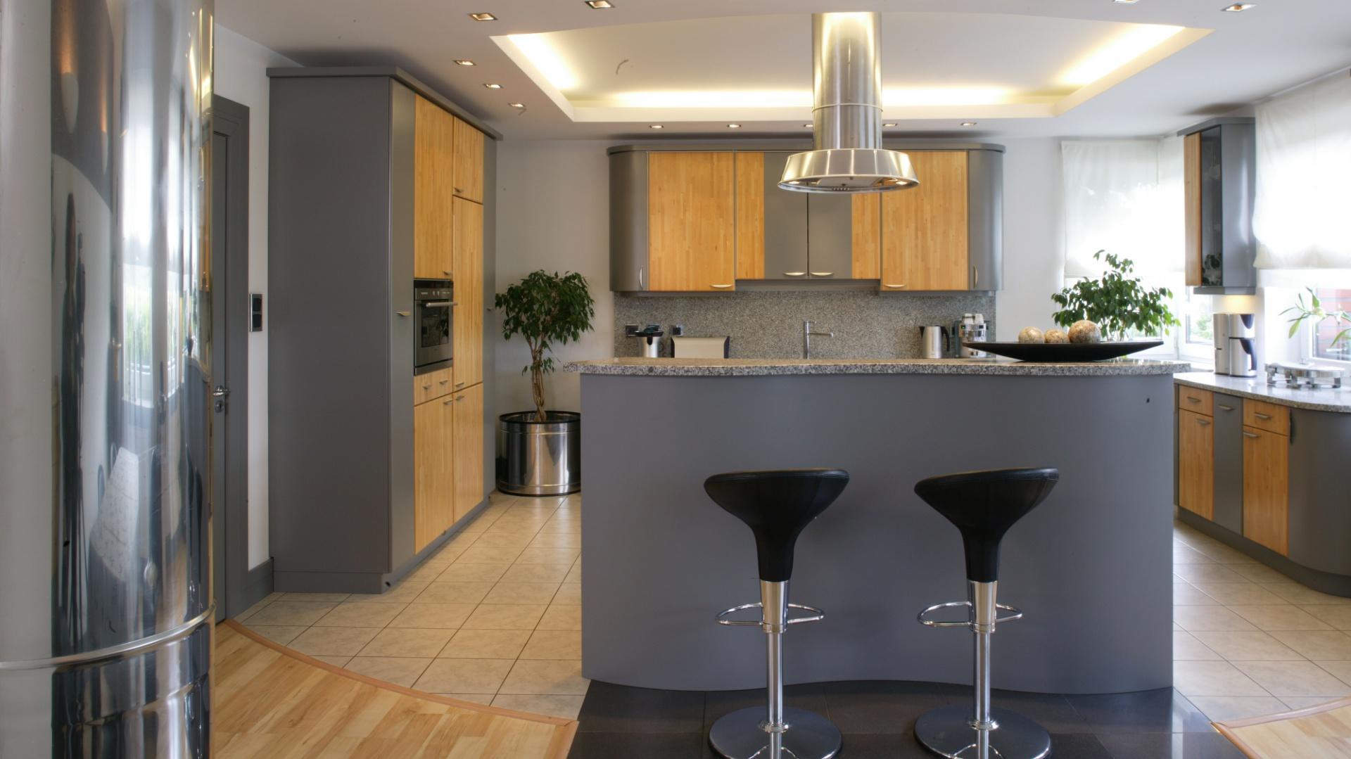 W kuchni centralne miejsce zajmuje wyspa, umownie rozdzielająca dwie strefy funkcjonalne. Umieszczony nad nią obniżony sufit, odpowiednio oświetlony, sprawia, że pomieszczenie optycznie wydaje się wyższe. Fot. Monika Filipiuk.
