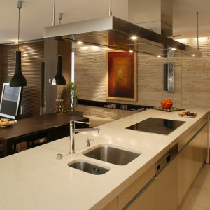 Długa, kuchenna wyspa pełni dwie funkcje. Od strony kuchni mieści w sobie zlew, kuchenkę elektryczną i szuflady na naczynia. Od strony salonu ma praktyczne półki na książki i drobiazgi. Fot. Tomek Markowski.