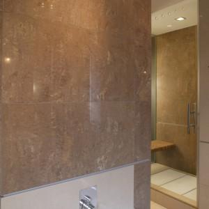 Ściany łazienki zostały wyłożone przypominającymi kamień płytami gresowymi w kolorze chłodnego brązu. Fot. Tomasz Markowski.