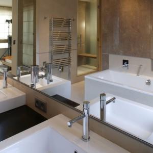 . W lustrze odbija się kabina prysznicowa, pełniąca także rolę sauny (dzięki zainstalowaniu wytwornicy pary i siedzisk z drewna tekowego). Trzy ściany obszernej kabiny (80x180 cm) wykonane są ze szkła, z czego jedna – wychodząca na hol przy garderobie – ze szkła nieprzezroczystego. Fot. Tomasz Markowski.