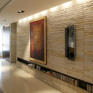 """Ściana z piaskowca z poziomą, kilkumetrową półką na kolekcję płyt CD. Z jej kolorem harmonizuje gresowy, jasny """"chodnik"""" na podłodze. Pierwsze drzwi prowadzą do sypialni, za kolejnymi kryje się wbudowany w ścianie gabinet. Fot. Tomek Markowski."""