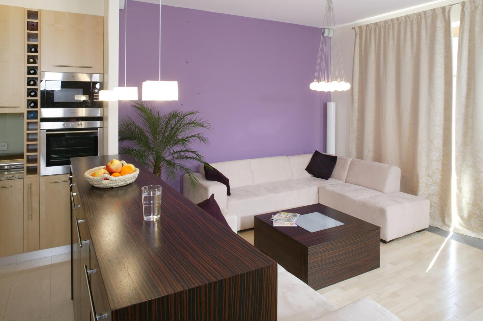 Fiolet, mocny kolorystycznie akcent na jednej ze ścian salonu, ciekawie komponuje się z kanapami obitymi elegancką alcantarą, jasnym jesionowym parkietem i grubymi kotarami o barwie delikatnego złota. Fot. Marcin Onufryjuk.